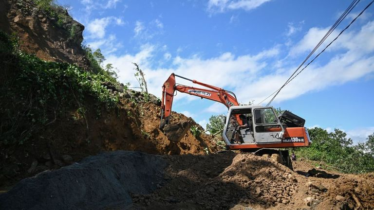 A worker in a bulldozer clears debris from a landslide that blocked a road