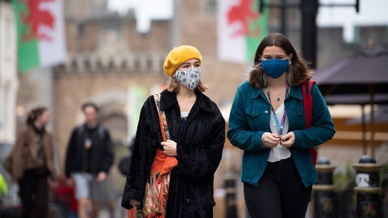 Two women wear face masks as they walk down St Mary Street near Cardiff Castle
