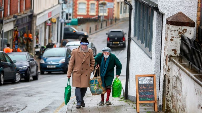 An elderly couple are seen wearing a visor and mask in Knighton, Wales
