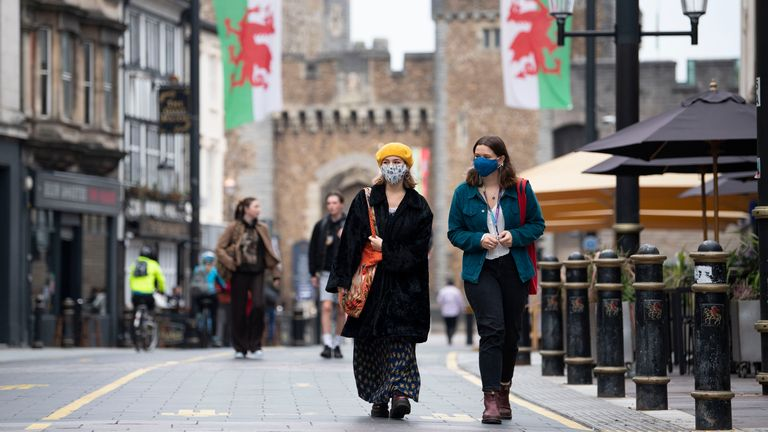 Two women wear face masks as they walk down St Mary Street near Cardiff Castle