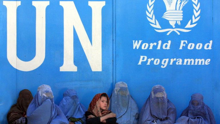 Afghan women sit in front of the UN World Food Programme (WFP) headquarters in Kabul