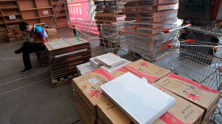 An employee sits on boxes of tiles at a closed Home Depot store in Zhengzhou, Henan province, September 14, 2012. When Wal-Mart Stores Inc drew a rush of 80,000 shoppers on the opening day of its first China supercentre in 1996, the world's most populous country looked like easy pickings for the top global retailers. Flash forward to 2012 and China has been a tougher market than expected.