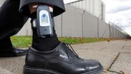 A man has an electronic tag attached to his ankle during a presentation of the device at a press conference in Stuttgart-Stammheim, Germany, 10 November 2010. After positive experience during test runs, more prisoners in the Baden-Wuerttemberg  