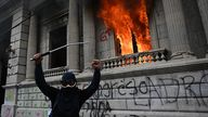 A protester celebrates as the congress building burns behind him