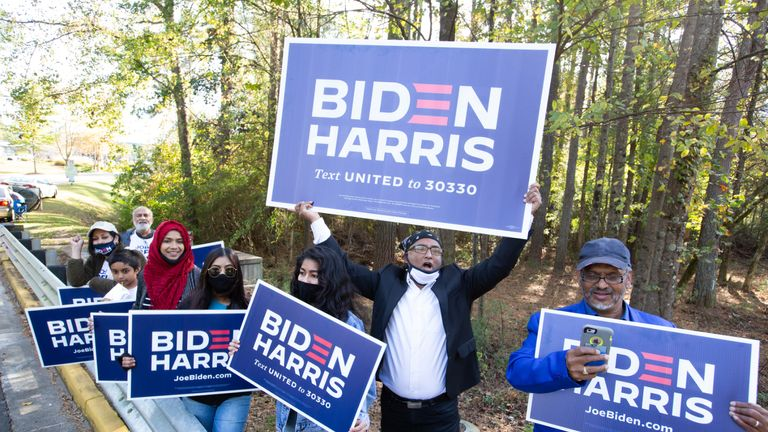 NORCROSS, GA - NOVEMBER 03: Gwinnett county voters including Menar Hague (C) wave Biden-Harris campaign signs at the entrance to Lucky Shoals Park polling station on November 3, 2020 in Norcross, Georgia. After a record-breaking early voting turnout, Americans head to the polls on the last day to cast their vote for incumbent U.S. President Donald Trump or Democratic nominee Joe Biden in the 2020 presidential election. (Photo by Jessica McGowan/Getty Images)