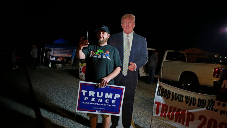 Voter Lerenzo Corralez takes a photograph with a President Trump cardboard cutout near Bob Ruud Community Center on Election Day on November 3, 2020, in Pahrump, Nevada. - Americans were voting on Tuesday under the shadow of a surging coronavirus pandemic to decide whether to reelect Republican Donald Trump, one of the most polarizing presidents in US history, or send Democrat Joe Biden to the White House. (Photo by Ronda Churchill / AFP) (Photo by RONDA CHURCHILL/AFP via Getty Images)