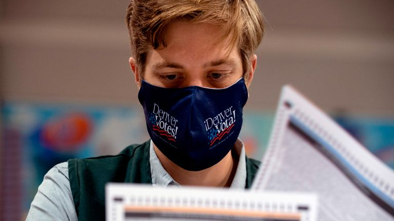A poll worker reviews voter ballots at the Denver Elections Division headquarters in Denver, Colorado on November 3, 2020. - Americans were voting on Tuesday under the shadow of a surging coronavirus pandemic to decide whether to reelect Republican Donald Trump, one of the most polarizing presidents in US history, or send Democrat Joe Biden to the White House. (Photo by Jason Connolly / AFP) (Photo by JASON CONNOLLY/AFP via Getty Images)