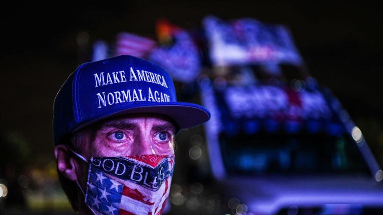 """TOPSHOT - Andy Soberon a supporter of the Democratic party attends a watch party in Miami, Florida on November 3, 2020. - The US is voting Tuesday in an election amounting to a referendum on Donald Trump's uniquely brash and bruising presidency, which Democratic opponent and frontrunner Joe Biden urged Americans to end to restore """"our democracy."""" (Photo by CHANDAN KHANNA / AFP) (Photo by CHANDAN KHANNA/AFP via Getty Images)"""