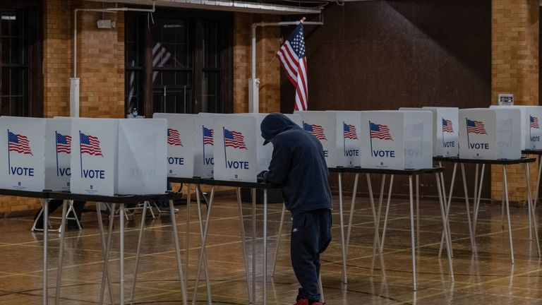 """A resident casts his vote on November 3, 2020, at Berston Fieldhouse in Flint, Michigan. - The US is voting Tuesday in an election amounting to a referendum on Donald Trump's uniquely brash and bruising presidency, which Democratic opponent and frontrunner Joe Biden urged Americans to end to restore """"our democracy."""" (Photo by Seth Herald / AFP) (Photo by SETH HERALD/AFP via Getty Images)"""