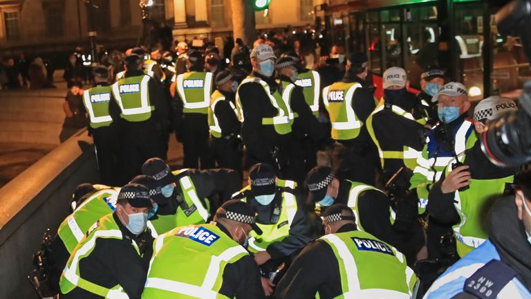 Police detain a protester during the Million Mask March anti-establishment protest at Trafalgar Square in London, on the first day of a four week national lockdown for England.