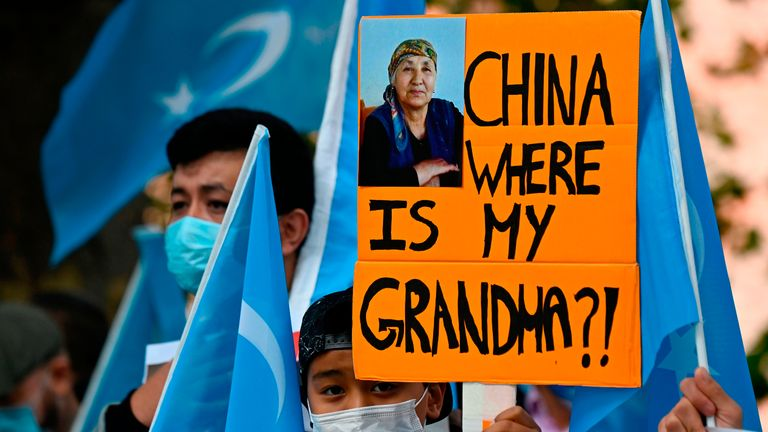 "A young Uyghur activist holds up a poster that reads ""China where is my grandma?!"" during a demonstration on September 1, 2020 outside the Foreign Office in Berlin, where the Chinese Foreign Minister was expected to hold talks with his German counterpart. (Photo by Tobias SCHWARZ / AFP) (Photo by TOBIAS SCHWARZ/AFP via Getty Images)"