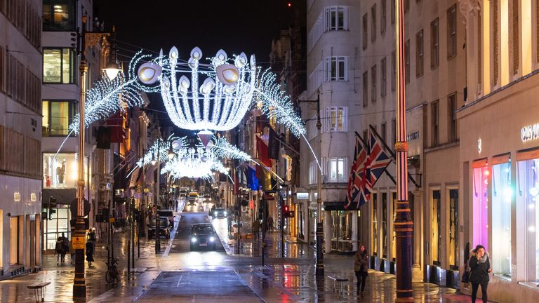 People walk under Christmas lights on Carnaby Street in central London, as England continues a four week national lockdown to curb the spread of coronavirus.