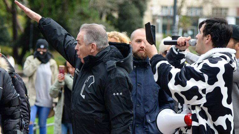 BOURNEMOUTH, ENGLAND - NOVEMBER 21: Anti-lockdown protester gestures to police officers during the march through the town centre on November 21, 2020 in Bournemouth, England. (Photo by Finnbarr Webster/Getty Images)