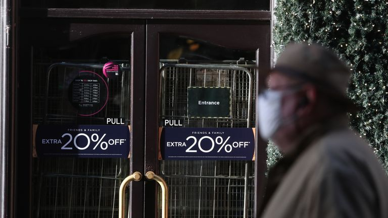 A man walks past the closed House of Fraser store on Buchanan Street in Glasgow on the first day after eleven local council areas in Scotland moved into Level 4 restrictions to slow the spread of coronavirus.