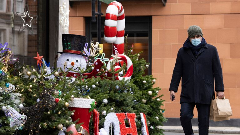LONDON, ENGLAND - NOVEMBER 23: A man wearing a facemask walks past Christmas decorations outside a wine shop in Mayfair on November 23, 2020 in London, England. UK Prime Minister, Boris Johnson, will announce plans for new coronavirus restrictions to the House of Commons once the current lockdown comes to an end on December 2nd. (Photo by Dan Kitwood/Getty Images)