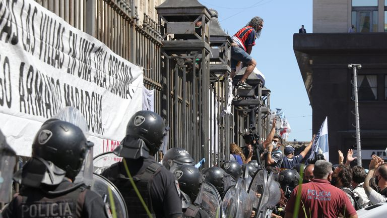 BUENOS AIRES, ARGENTINA - NOVEMBER 26: Police officers try to set a barricade next to the fence of Casa Rosada as riots start and fans attempt to climb over during Diego Maradona's funeral on November 26, 2020 in Buenos Aires, Argentina. Maradona died of a heart attack at his home on Thursday 25 aged 60 . He is considered among the best footballers in history and lead his national team to the World Cup in 1986. President of Argentina Alberto Fernandez declared three days of national mourning. (Photo by Federico Peretti/Getty Images)