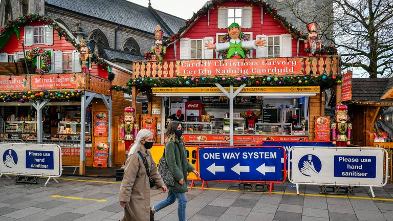 "People pass Christmas market stalls in Cardiff, where restrictions across Wales have been relaxed following a two-week ""firebreak"" lockdown."