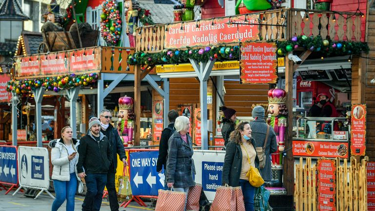 "Shoppers pass Christmas market stalls in Cardiff, where restrictions across Wales have been relaxed following a two-week ""firebreak"" lockdown."
