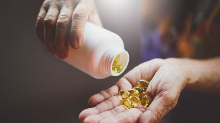 Image of Bottle of omega 3 fish oil capsules pouring into hand.
