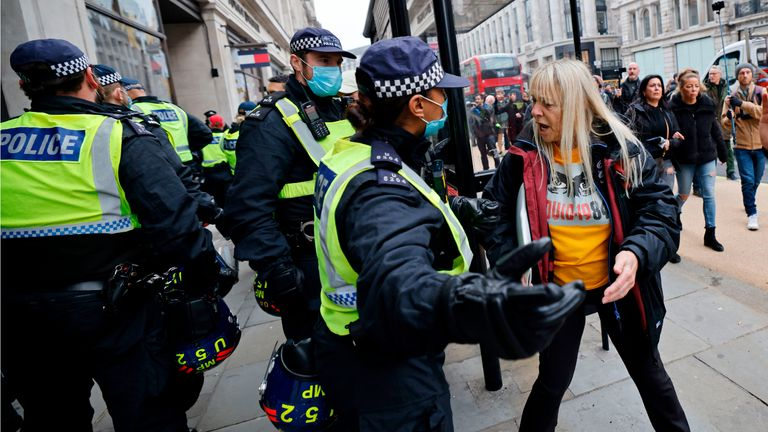 Police officers wearing a protective face coverings to combat the spread of the coronavirus covid-19 speak with a protester during an anti-lockdown protest against government restrictions designed to control or mitigate the spread of the novel coronavirus, including the wearing of masks and lockdowns, on Regents Street in London on November 28, 2020. (Photo by Tolga Akmen / AFP) (Photo by TOLGA AKMEN/AFP via Getty Images)