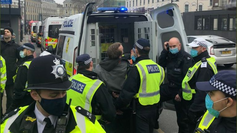 A man is detained by police during an anti-lockdown protest in London