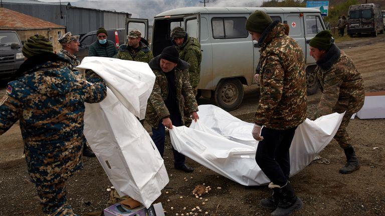 جنود أرمن يجمعون جثث الجنود الذين قُتلوا في القتال من أجل أذربيجان على الطريق حيث اندلعت الأيام الأخيرة من المعركة بين الجيشين ، في 13 نوفمبر 2020 في ستيباناكيرت ، أذربيجان.