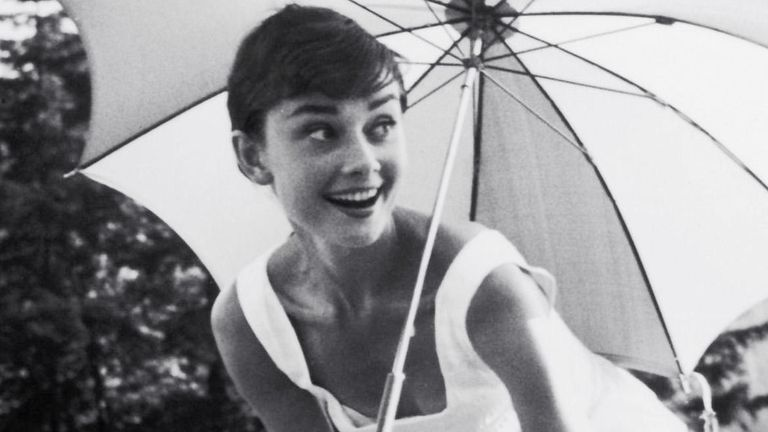 PMC49Y Audrey Hepburn playing golf and holding a parasol, circa 1955. Pic: PictureLux /The Hollywood Archive /Alamy Stock Photo