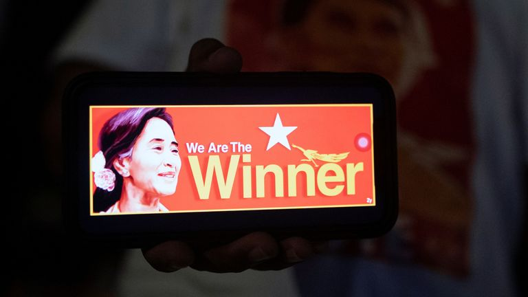 A person shows a picture of Myanmar State Counselor Aung San Suu Kyi on a mobile phone as supporters of the National League for Democracy (NLD) party wait for results outside the party headquarters, after the general election in Yangon, Myanmar, November 8, 2020.?REUTERS/Shwe Paw Mya Tin