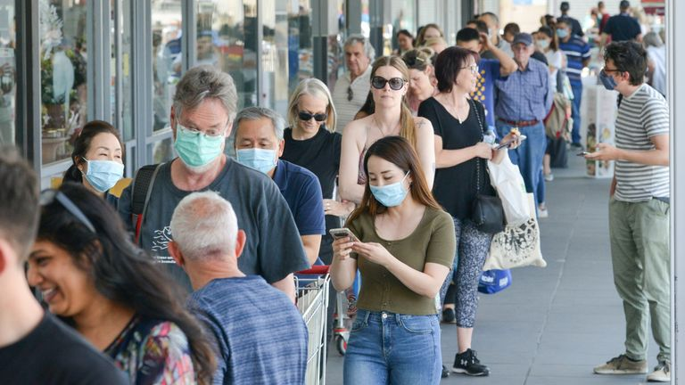 People are seen queuing outside a supermarket after Australia's lockdown measures came into force