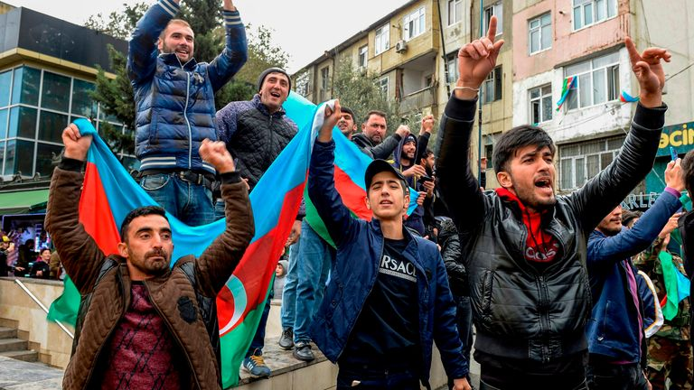 People hold the Azeri flag as they celebrate the capture the town of Shusha