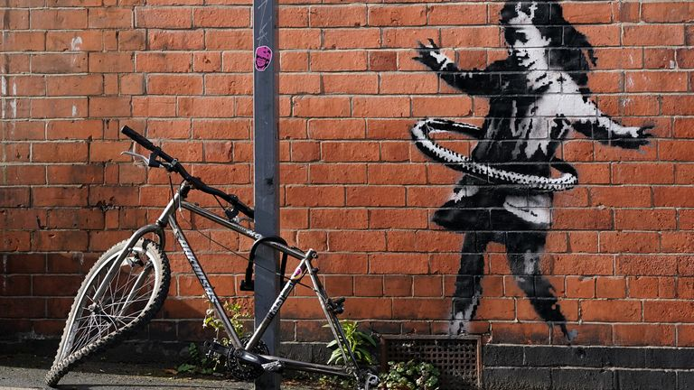 The artwork depicts a young girl playing with a tyre and was painted on a wall near to an abandoned bicycle