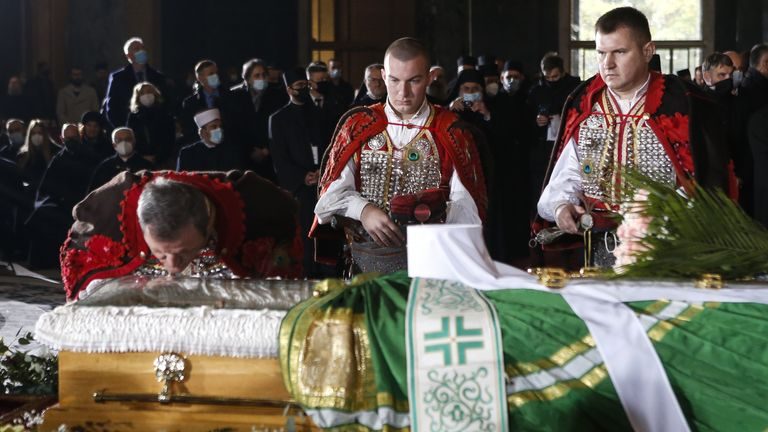 A man kisses the coffin of Patriarch Irinej during the funeral procession in St. Sava Temple