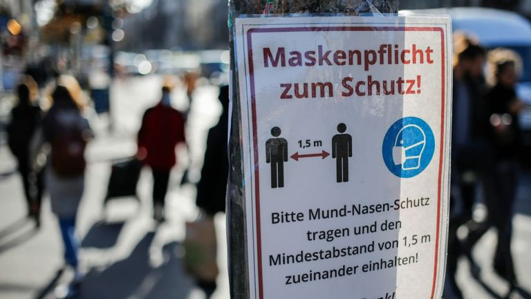 People cross the road past a sign calling on people to wear face masks and observe social distancing rules in Berlin's Kreuzberg district on November 5, 2020 amid the novel coronavirus COVID-19 pandemic. (Photo by David GANNON / AFP) (Photo by DAVID GANNON/AFP via Getty Images)