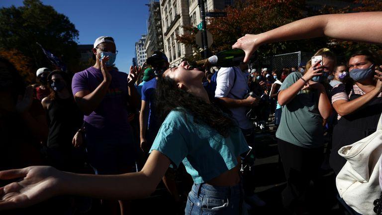 People react as media announce that Democratic U.S. presidential nominee Joe Biden has won the 2020 U.S. presidential election, on Black Lives Matter Plaza in Washington, U.S., November 7, 2020. REUTERS/Hannah McKay