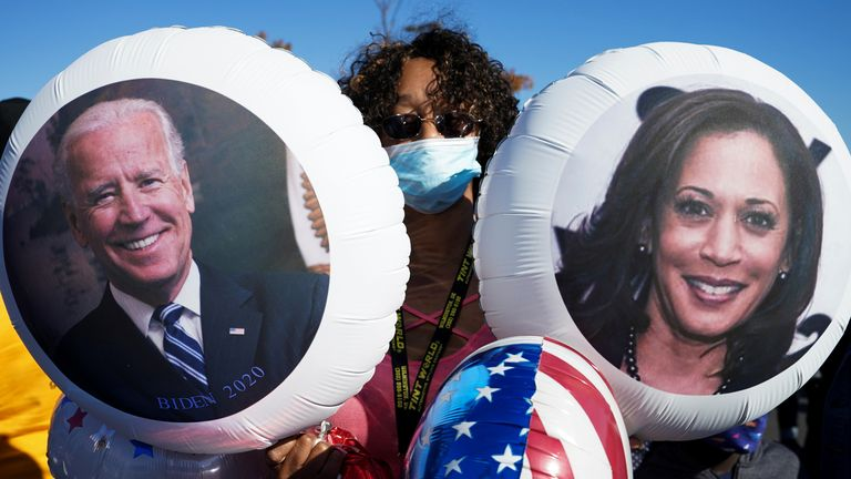 A supporter of Democratic U.S. presidential nominee Joe Biden holds balloons with the faces of Joe Biden and Kamala Harris as she celebrates near the site of a planned election victory celebration after news media declared Biden to be the winner of the 2020 U.S. presidential election in Wilmington, Delaware, U.S., November 7, 2020. REUTERS/Kevin Lamarque