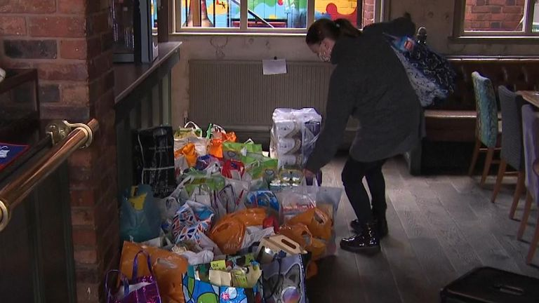 A woman drops off items for the food bank