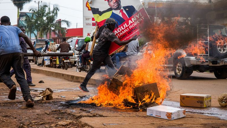 A Bobi Wine supporter carrying a campaign poster during protests
