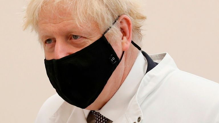 Britain's Prime Minister Boris Johnson wears a mask because of the novel coronavirus pandemic as he visits the Public Health England site at Porton Down science park near Salisbury