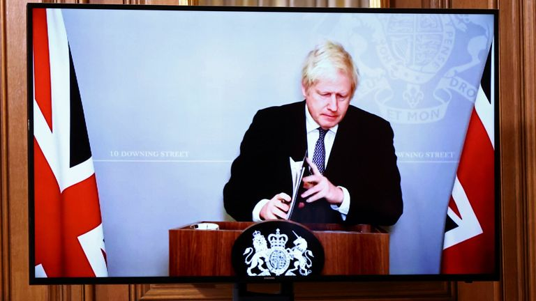 On screen due to self-isolating, Boris Johnson holds a virtual news conference inside 10 Downing Street