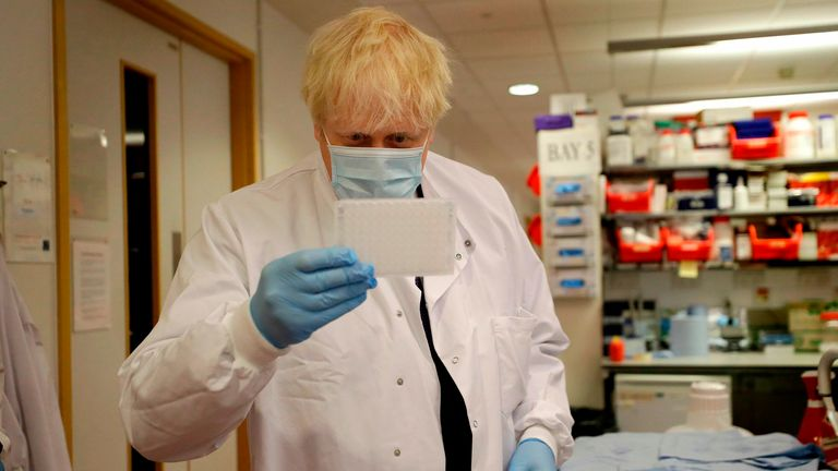 Britain's Prime Minister Boris Johnson looks at an immunological assay as he washes them during a visit to the Jenner Institute in Oxford, central England, on September 18, 2020, where the Prime Minister toured the laboratory and met scientists who are leading the covid-19 vaccine research. - Millions more people in northern and central England faced new restrictions over a surge in coronavirus cases, the British government announced on Friday, as it warned another national lockdown could be imm