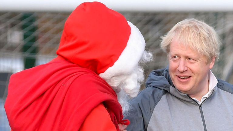 CHEADLE HULME, UNITED KINGDOM - DECEMBER 07: British Prime Minister Boris Johnson jokes with a man dressed as Father Christmas during the warm up before a girls' soccer match between Hazel Grove United JFC and Poynton Juniors on December 7, 2019 in Cheadle Hulme, United Kingdom. The Prime Minister is campaigning in the North West ahead general election on December 12. (Photo by Toby Melville - WPA Pool/Getty Images)