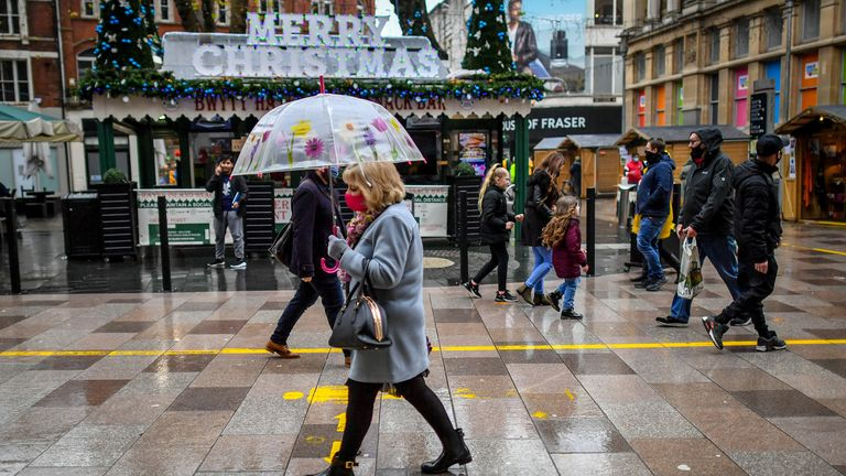 A woman walks past a Christmas sign in the centre of Cardiff
