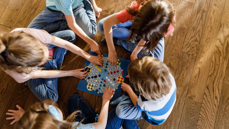 High angle view of group of small friends playing ludo game on wooden floor at home.