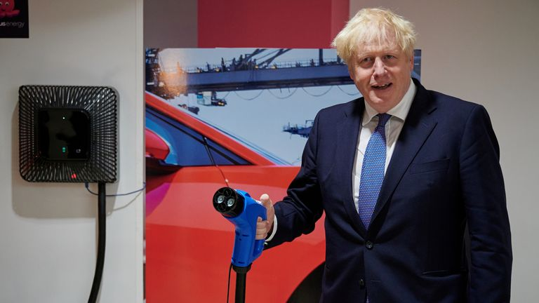 Boris Johnson holds an electric vehicle charging cable