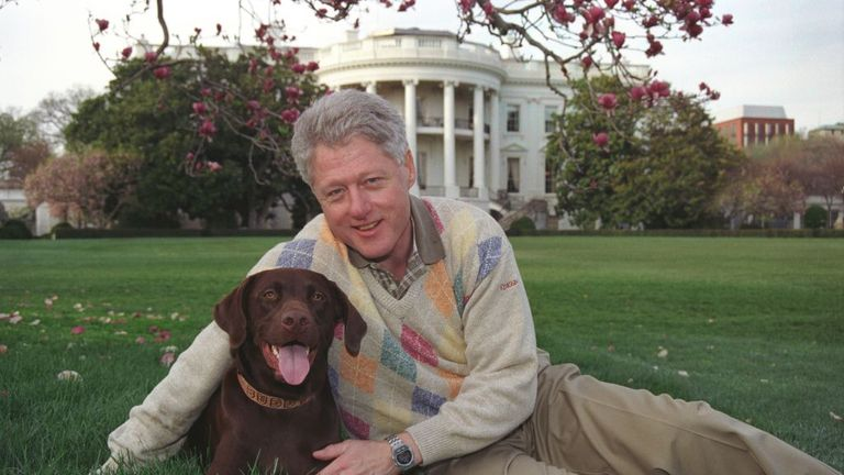 President William Jefferson Clinton posing with Buddy the Dog outside of the White House, April 6, 1999. Image courtesy National Archives. (Photo via Smith Collection/Gado/Getty Images).