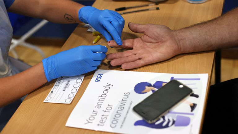 A worker takes a blood sample from a man during a clinical trial