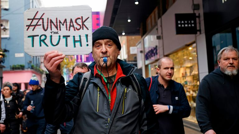 A protester holds up a placard as he takes part in an anti-lockdown protest against government restrictions designed to control or mitigate the spread of the novel coronavirus, including the wearing of masks and lockdowns, in London on November 28, 2020. (Photo by Tolga Akmen / AFP) (Photo by TOLGA AKMEN/AFP via Getty Images)