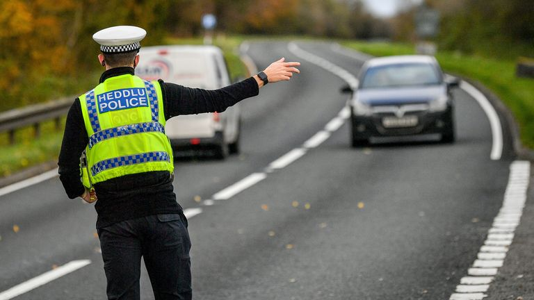 Police pull over cars at a checkpoint during Wales's 'fire break' lockdown