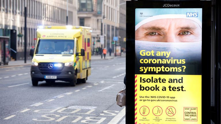 An ambulance drives past a sign displaying the measures imposed by the government against the outbreak of the coronavirus disease