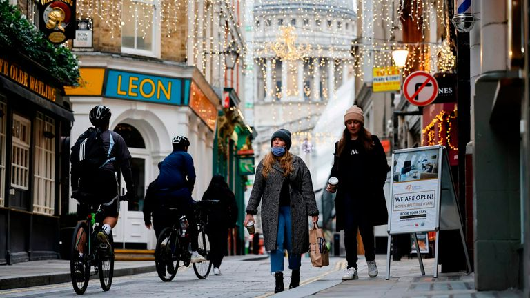 Pedestrians and cyclists make their way through the streets of the City of London in London